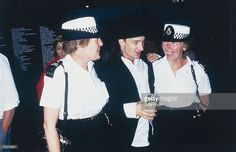 Bono of U2 makes friends with a couple of female police officers backstage at Wembley Stadium during the Live Aid Concert, 13th July 1985.