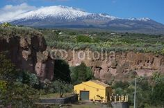 Yellow house in a canyon with Etna volcano's background, Sicily