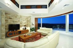 The living room featuring that gorgeous stone wall and looking out towards the view!