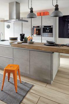 Grifflose Betonküche mit Pultplatte als Tresen. Toll dazu: Orangfarbene Accessoires wie der knallige Metallhocker in Orange