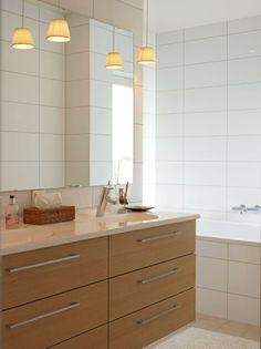 Badet er dekket av store hvite fliser, som også dekker badekaret. Baderomsmøbelet er i lyst tre, og med to vaskeservanter.