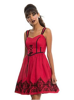 """<div>Steal the show and take over the room the minute you step in wearing this dress! The red fit and flare dress has adjustable button wide straps so they'll never slip! The bodice features a sweetheart neckline and contrasting black piping. A fitted, black lace-up accented waist leads to a full circle skirt with black flocked skull cameo and roses print. Side zipper closure.</div><div><ul><li style=""""list-style-position: outside !important; list-style-type: disc !important;"""">97% cotto..."""