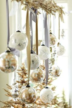 Hang ornaments from metallic ribbons and garland for a festive flair - ideas via harpersbazaar.com
