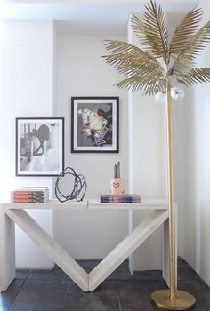 """""""This corner of the living room features our pièce de résistance,"""" Mat says, """"a gorgeous 7-foot brass palm tree floor lamp by MVNGMNTS."""" The arrow console table and books are from Consort, and the small blush and gold lips vase is by Lux/Eros. The neon artwork is by Andrew Arthur."""