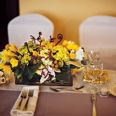 Brides: Yellow Bloom and Succulent Centerpiece . The reception was held inside the mansion, where tables displayed centerpieces of dusty miller, daffodils, hydrangeas, craspedia, succulents, fiddleheads, and ranunculuses. All floral design was by Fleur de Lys.