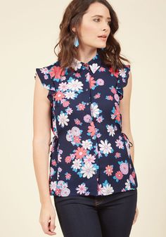 <p>Your pep and your push are both sought-after assets, and together with this midnight blue blouse they bring you brilliant success! Part of our ModCloth namesake label, this fluttery top flaunts a pulled-together collar, side ties to cinch its buttoned silhouette, and a pink, coral, white, and blue flower pattern. Thanks to these deets, you'll prosper looking polished!</p>