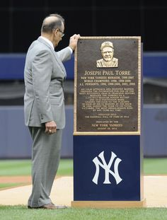 Former New York Yankees manager Joe Torre looks at a replica of his plaque that will hang in Monument Park as the Yankees retired his number before a baseball game against the Chicago White Sox Saturday, Aug. 23, 2014