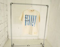 太陽光を利用したシルクスクリーンでの手刷りのTシャツ。ブルーのストライプペイントの上にロゴと木馬のモチーフをプリントしました。中央のコッパーのプリントとスラッ...|ハンドメイド、手作り、手仕事品の通販・販売・購入ならCreema。