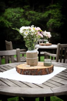 Outdoor table simple centerpiece-- vintage mason jars all with different lace/burlap/pearl decor on a sliced tree!
