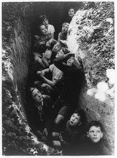 Curiosity overrode fear in the faces of these English children taking shelter in a ditch during a German air raid, 1940