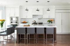 contemporary white kitchen, stained wood island, sleek gray and chrome counter stools