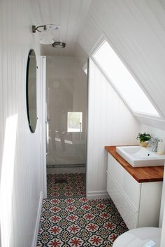 Small bathroom with slanted ceilings and Moroccan style tiles on the floor.