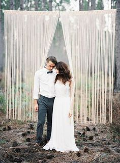 It's not just indoor weddings that benefit from backdrops. Outdoor ceremonies also shine with the help of these projects. In fact, a backdrop often helps focus in, despite all the open space. It can transform a field or forest grove into your wedding venue, which is no easy feat.  Above, tree branches prove handy when hanging this curtain of metallic fringe for a rustic-chic event.