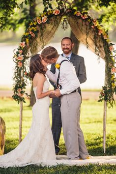 a flower adorned arch is also draped with burlap and a small lantern for that added detail on this wedding alter - thereddirtbride.com - see more of this wedding here
