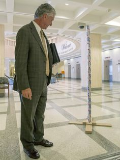 Florida lobbyist Keith Arnold stops to look at Chaz Stevens' Festivus pole made out of beer cans in the rotunda of the Florida Capitol in Ta...