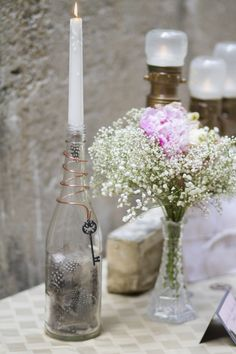 There's such simplicity in the vase - rose with babys breath. Also, love the candle in the wine bottle!