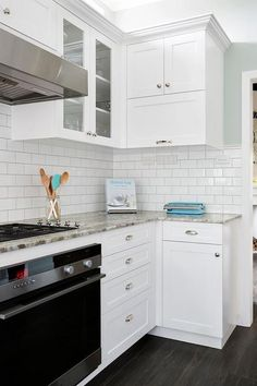 Beautiful kitchen features white cabinets paired with Fantasy Brown Granite countertops in a leather finish alongside half the wall clad in subway tiles and the other half painted robin egg's blue.