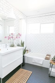 Mid Century Modern Bathroom With White Subway Tiles On The Walls And Black Hexagon Ones