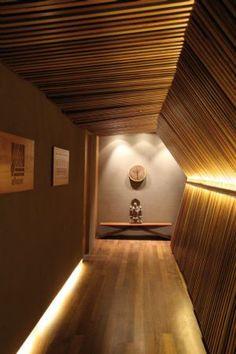Luz indireta valoriza nuances e texturas da madeira que reveste corredor da Ecolog, em Barueri, SP, criado pelo Rethink Space Arquitetura