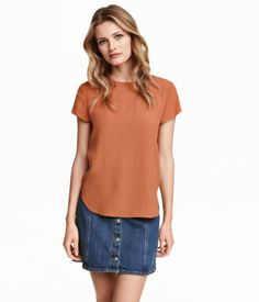 Short-sleeved, gently flared blouse in woven crêpe fabric with a button at back of neck. Rounded hem, slightly longer at back.