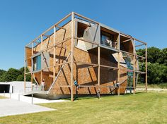 designed for an austrian facade systems company, the building's envelope of intersecting folded planes contrasts its larger timber structural grid.
