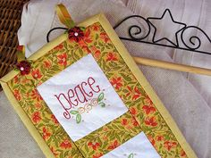 Quilted Christmas wall hanging tutorial with embroidered squares: Peace, Joy, Love, Hope
