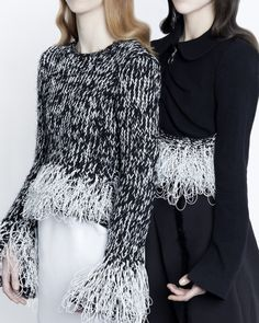 These sweaters look to be cotton and have fringe on them to give the sweater more texture.