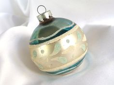 This vintage, large, silver and teal Christmas ornament is awesome! It has a matte silver band in the middle with white and aqua mica leaf shapes.