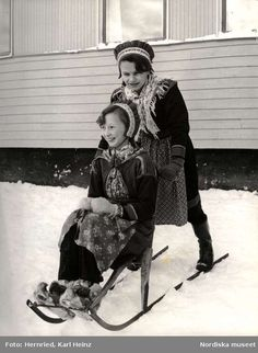 Two sami girls going for a ride on a sparkstötting (≈ kick sled), The Nomad School (Nomadskolan) in Gällivare, Lappland, Sweden.