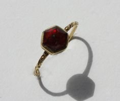 "A ""ruby"" ring of 18 carat gold with a foliate shank in hexagonal shape with a high rose cut rock crystal, Dutch or German, around 1580."