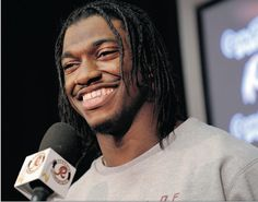Redskins quarterback Robert Griffin III smiles as he asks coach Mike Shanahan a question at a news conference following his team's practice Wednesday.