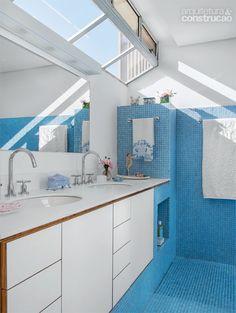 Apartamento tem todo o piso revestido com pastilhas azuis - Casa A luz serena irrompe nas janelas, que deixam entrever o céu. Aqui, o azul escala as paredes do boxe. Bancada de Corian (DuPont) e metais da Deca. Projeto de Angelo Bucci.