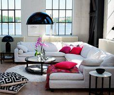 salon de style scandinave avec un canapé blanc, coussins en blanc et magenta, suspension et lampe de chevet noires