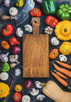 #Fall harvest colorful vegetable set  Tomatoes onions mushrooms carrots pumpkin patissons garlic spices and knives on dark blue grunge plywood background with wooden chopping board in center. Top view copy space