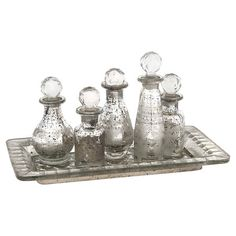 A vintage-inspired addition to your console table or sideboard, this 6-piece mercury glass bottle and tray set showcases crystal-inspired stoppers and a dist...