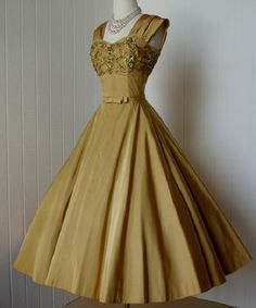1950's cocktail party dress in matte gold taffeta, fitted bust with pleated bodice under netted overlay embellished with gold ribbon, sequins, and beads, wide pleated shoulder straps, full circle skirt with tulle net lining. (Matching bolero jacket) No maker label