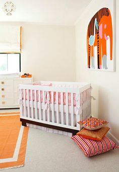 Chic orange nursery features orange elephant art on ivory walls framing white crib dressed in Annette Tatum Crib Bedding Set, pink crib bedding accented with white and pink striped crib skirt, next to white art deco changing table with brass hardware over orange border rug.