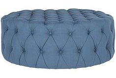 This luxurious upholstered ottoman features blue fabric and generous button tufting.