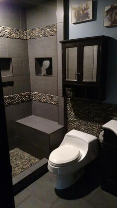 Masculine bathroom remodel using Bali Ocean Standing Pebble Tile on wall and shower accents. https://www.pebbletileshop.com/products/Bali-Ocean-Standing-Pebble-Tile.html#.Vm8JjbiDFBc