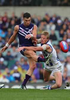 Liam Anthony of the Kangaroos attempts to smother the kick by Ryan Crowley of the Dockers during the round 13 AFL match between the Fremantle Dockers and the North Melbourne Kangaroos at Patersons Stadium on June 2013 in Perth, Australia. Australian Football League, Perth Australia, Kangaroos, Crowley, Melbourne, Kicks, June, Strong, Club