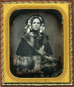 An attractive, very self-possessed woman of the 1840s. Her fur-trimmed cloak and elaborately decorated bonnet are ceraintly signs of status.