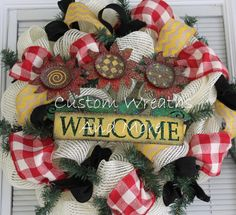 adorable sunflower welcome sign in a cream mesh wreath, red and white gingham ribbon, black ribbon, and yellow burlap chevron ribbon. Truly a must see. Pictures dont do any justice. Perfect mothers day gift. mothers day wreath, summer wreath, outdoor wreath, mesh wreath, burlap wreath and more