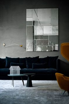 Interesting moody color scheme:  deep green and yellow velvet chairs, cool gray carpet; warm gray walls.