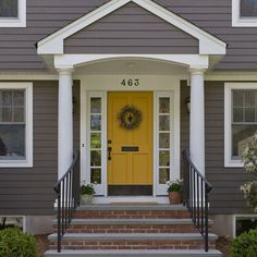 Golden yellow door on dark grey house with white trim