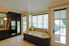 Wood paneling around the soaking tub in this neutral bathroom makes it feel more like a piece of custom furniture. Custom fit shades provide privacy while still keeping the room feeling light and open. The black cabinets create a beautiful and sophisticated contrast against the neutral tile, countertop and walls.