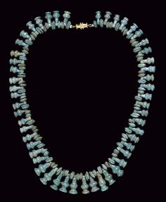 AN EGYPTIAN FAIENCE BEAD NECKLACE   NEW KINGDOM, DYNASTY XVIII-XX, 1550-1070 B.C.   Composed of fifty-two blue lotus-seed pendants, interspersed with floral rosettes and disk-shaped beads; strung with a modern gold clasp  14½ in. (37 cm.) long