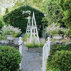 Using it all in this garden - gravel path, stone walls, green walls, planters, obelisk, raised beds, gate.