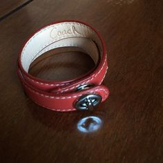 Coach Leather Wrap Bracelet with Turnlock Close Light red all-leather wrap bracelet with silver turnlock closure from Coach! New without tags and never worn, this bracelet is in perfect condition. I received this as a gift but it unfortunately does not fit my giant wrists, haha. Adds a great pop of color to any outfit, and perfect for stacking with other bangles. Coach Jewelry Bracelets