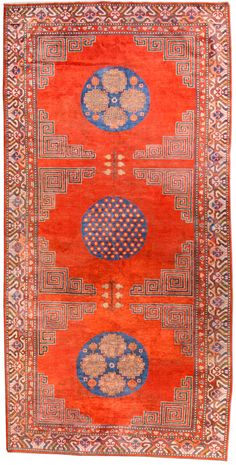 A silk Samarkand rug BB4577 - An antique silk Samarkand (Khotan) rug from the early 20th century, the open orange-red field around three blue ...