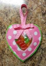 Candy Heart is an  in the Hoop Design of a heart pocket with a clear plastic window.  The ehart  can be filled with candy for a Valentine gift